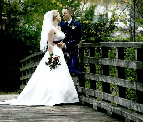 Wedding couple on bridge over River Tawe at Craig y Nos Country Park, Brecon Beacons