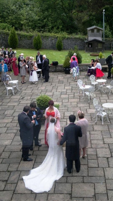 Wedding Guests gather on the large theatre terrace at Craig y Nos Castle wedding venue in the Brecon Beacons
